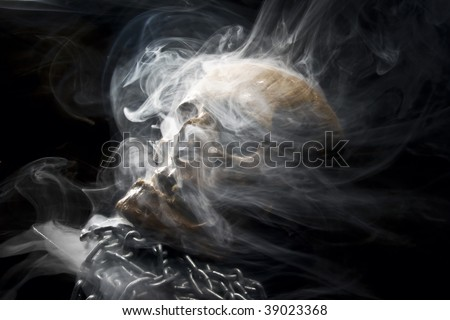front of real skull with chain in abstract smoke - stock photo