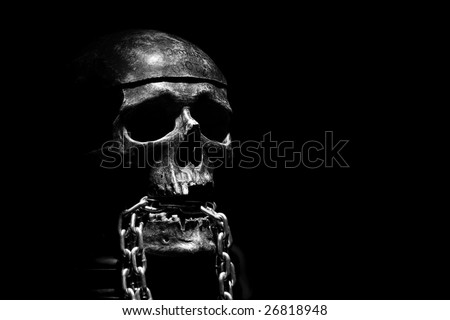 front of real skull with metal chain - stock photo