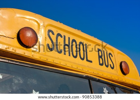 front of yellow school bus against blue sky - stock photo