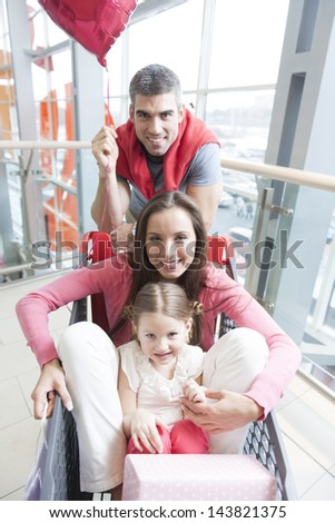 Front on view of mother and young daughter in trolley with father pushing - stock photo