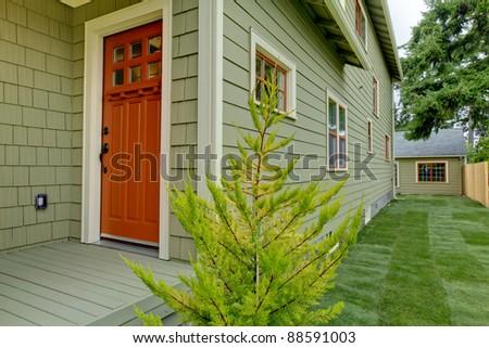 Front orange door of the green house . - stock photo