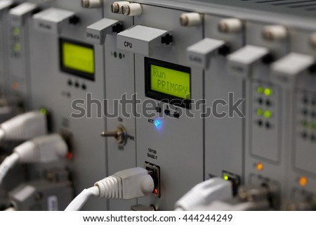 Front panel of industrial computer system with I/O ethernet connectors and cables. Selective focus on primary CPU module.
