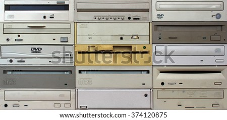 Front panels of old floppy cd and dvd drives as background - stock photo