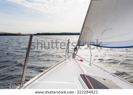 Front part of yacht swimming on lake. Beutiful Mazury lake photographed from yacht.