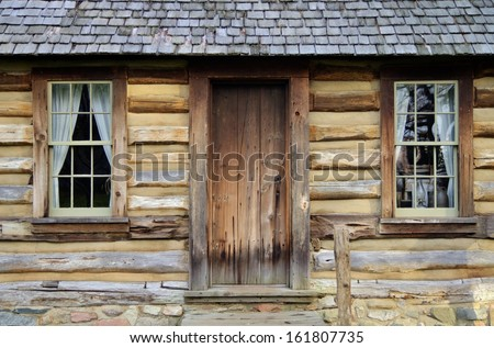 Front porch and windows of a historical pioneer log cabin. Pt. Sanilac Historical Village. Pt. Sanilac, Michigan.  - stock photo