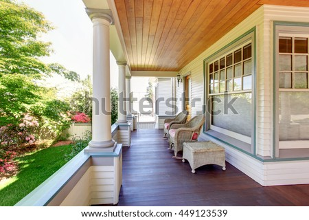 Front porch with chairs and columns of craftsman style home. - stock photo