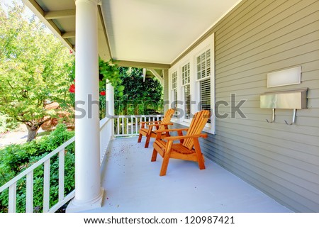 Front porch with chairs and columns of old craftsman style home.