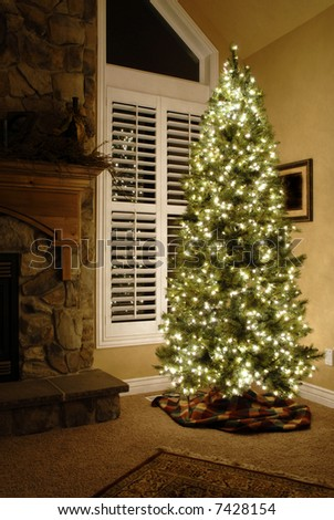Front room of home next to window decorated for christmas with tree - stock photo