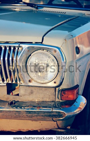 Front round headlight old car in bad condition. Retro toning. - stock photo