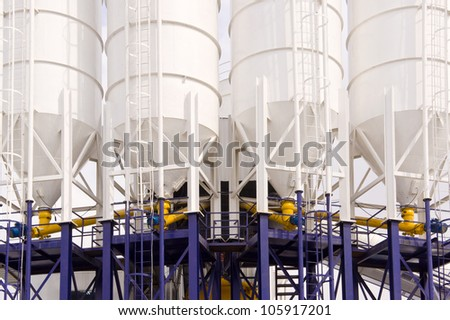 Front shot of four Industrial chemical processing Tanks. - stock photo
