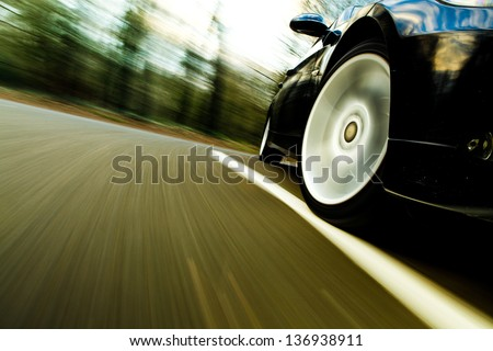 Front side view of black car driving fast. - stock photo