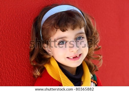 front teeth indented little girl smiling on a red wall background - stock photo