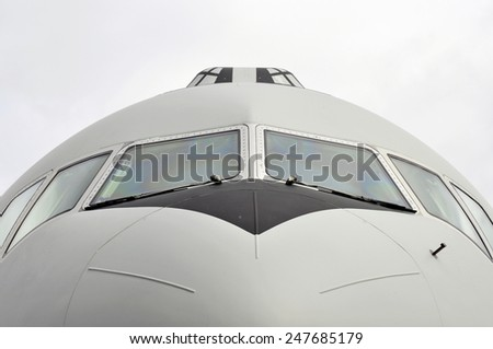 Front view close-up of a transportation airplane with cloudy sky - stock photo