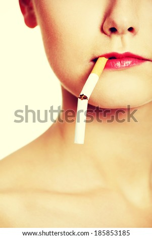 Front view face closeup holding a broken cigarette in lips - stock photo