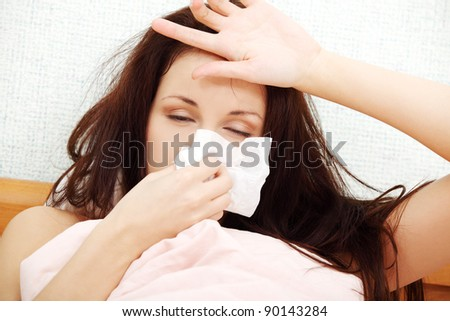 Front view face closeup of a beautiful young woman lying in bed, having a cold, sneezing in a tissue and resting her hand on the forehead. - stock photo