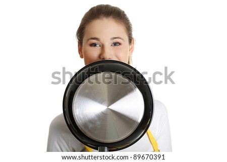 Front view face closeup of a young smiling caucasian female teen dressed in apron, smiling behind the frying pan, on white. - stock photo