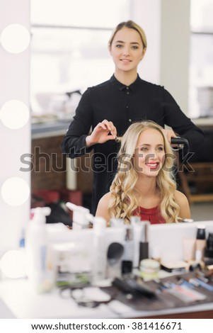 front view, happy a young woman getting her hair curled by beautician at parlor - stock photo