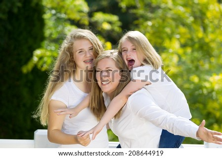 Front view, looking forward, of mother holding her younger daughter with older daughter hugging them while outdoors on patio with blurred out woods in background  - stock photo