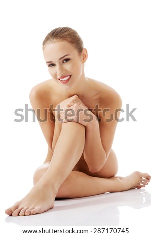 Front view nude woman sitting on the floor. - stock photo