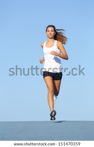 Front view of a beautiful sportswoman running towards camera with the blue sky in the background - stock photo