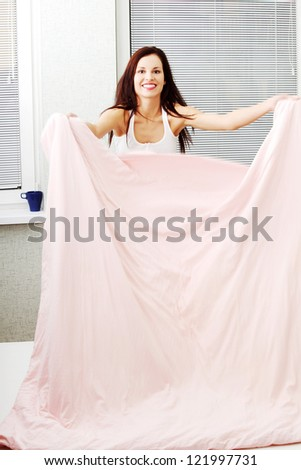 Front view of a beautiful young smiling woman doing the bed at home in the morning.