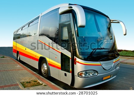 Front view of a big modern tour bus parked by the side of the road