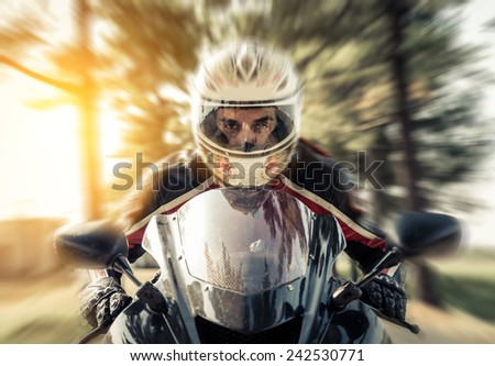 front view of a biker riding his sport motorcycle. concept about transportation - stock photo