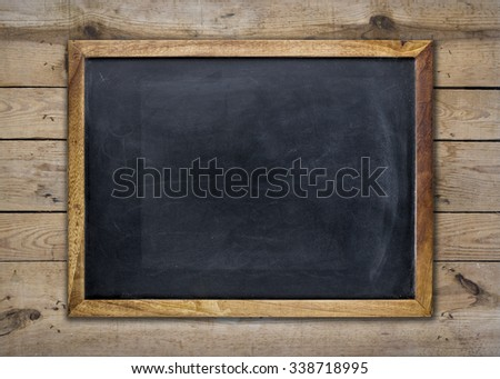 Front view of a blank blackboard over a weathered wooden surface - stock photo