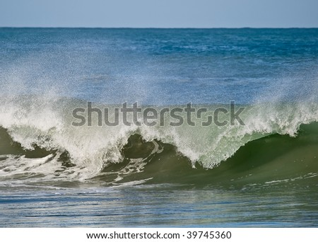 Front view of a breaking wave. The movement has been frozen using a fast shutter speed - stock photo