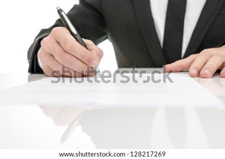 Front view of a business man signing a contract. With reflection on a white table. - stock photo