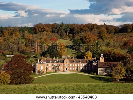 Front view of a country manor on an estate in rural Oxfordshire, England, in autumn. Photo taken in warm morning light with dramatic cloudy sky overhead.