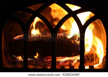 Front view of a cozy indoor fireplace with decorative metal doors - stock photo