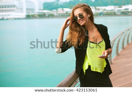 Front view of a fashion happy woman walking and using a smart phone on a city street,laughing and screaming on the street,wear cool aviator sunglasses and listen music on mp3 player,phone ,cool style  - stock photo