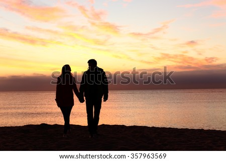 Front view of a full body of couple silhouettes holding hands and walking together looking each other in a date at sunset on the beach - stock photo