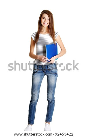 Front view of a full young happy female caucasian student holding a notebook, on white.