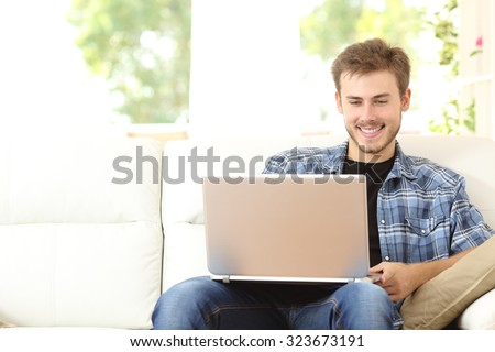 Front view of a handsome man using a laptop sitting on couch at home - stock photo