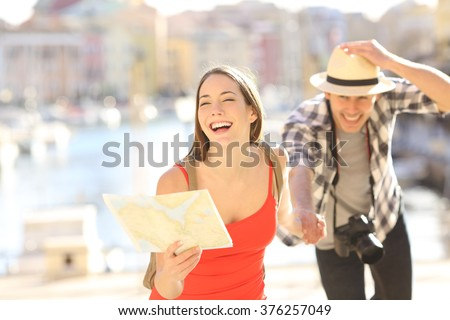 Front view of a happy couple of tourists running towards camera holding a paper map in a travel destination port with the sea in the background. Tourism concept - stock photo