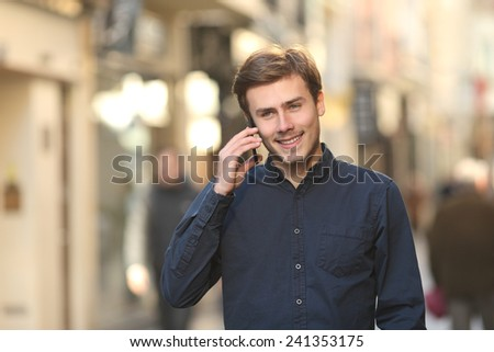 Front view of a happy man calling on the phone walking on the street - stock photo