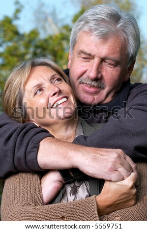 Front view of a mature couple smiling to each other. - stock photo
