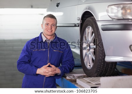 Front view of a mechanic next to a car in a garage - stock photo