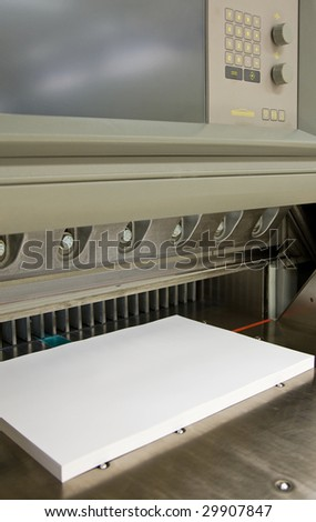Front view of a modern paper guillotine with touch screen used in commercial printing industry