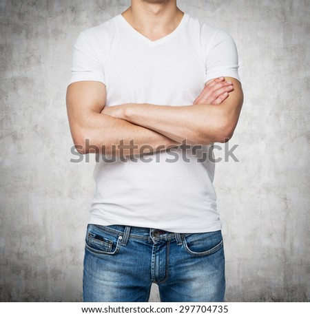 Front view of a person in a white V shape t-shirt with crossed hands. Concrete wall on background. - stock photo