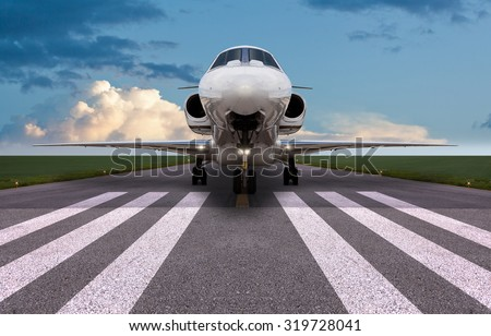 Front view of a private jet on the runway - stock photo