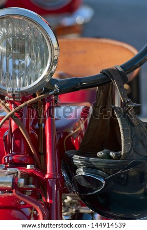 Front view of a red veteran motorbike with hanging helmet. - stock photo