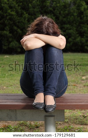 Front view of a teenager lonely depressed and sadness in a park - stock photo