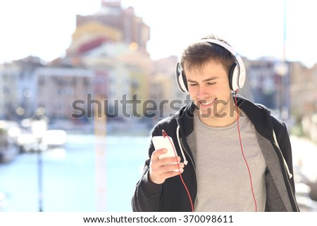 Front view of a teenager walking towards camera listening music with headphones from smart phone in a vacations destination - stock photo