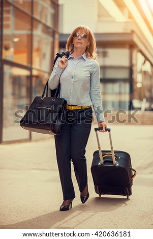 Front view of a traveler woman walking in an airport - stock photo