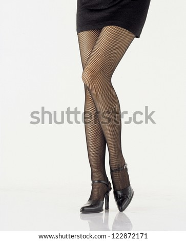 Front view of a woman's leg in fishnet hosiery - stock photo
