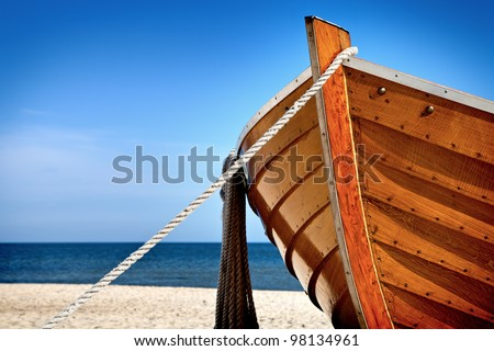 Front view of a wooden fishing boat, sea in background and blue sky with copyspace - stock photo