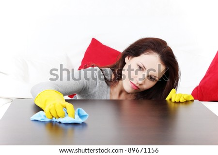 Front view of a young beautiful woman cleaning up the table at home.